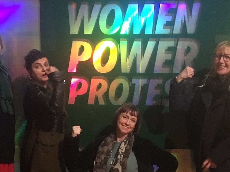 Space Invaders steering committee pose with power arms in front of the Women Power Protest holographic sign
